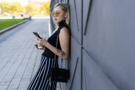 Fashionable young woman leaning against wall looking at smartphone - GIOF06246