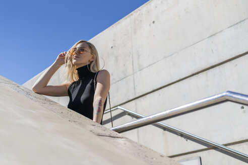 Portrait of blond young woman on stairs looking at distance - GIOF06252
