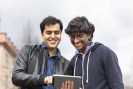 Portrait of smiling friends using mini tablet outdoors - SGF02368