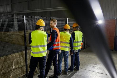 Rear view of workers standing in factory workshop - ZEDF02081