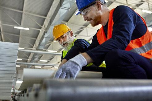 Two men working on plan in factory - ZEDF02087