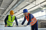 Two men working on plan in factory - ZEDF02096