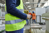 Close-up of worker wearing reflective vest in factory - ZEDF02099
