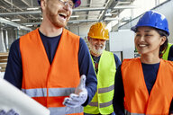 Happy colleagues in protective workwear talking in factory - ZEDF02102