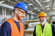 Happy colleagues in protective workwear talking in factory - ZEDF02105