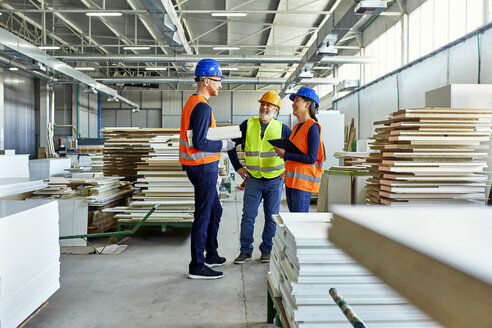 Colleagues in protective workwear talking in factory - ZEDF02111