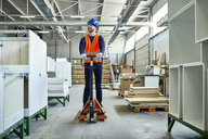 Worker riding on pallet jack in factory - ZEDF02114