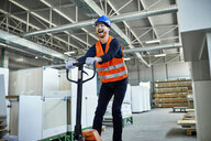 Laughing worker riding on pallet jack in factory - ZEDF02117