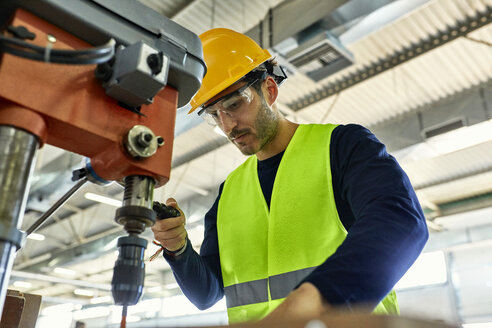 Worker operating drill in factory - ZEDF02141