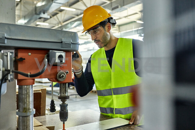 Worker operating drill in factory - ZEDF02144