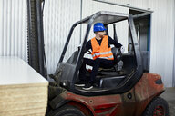 Worker on forklift in factory turning round - ZEDF02147