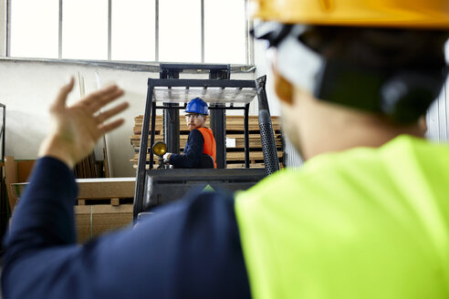 Worker assisting man on forklift in factory - ZEDF02150