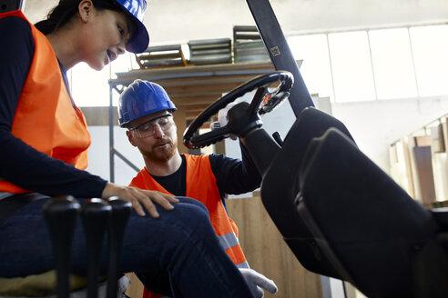 Man instructing female worker on forklift in factory - ZEDF02153