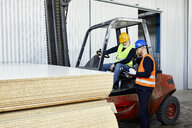 Man talking to worker on forklift in factory - ZEDF02159