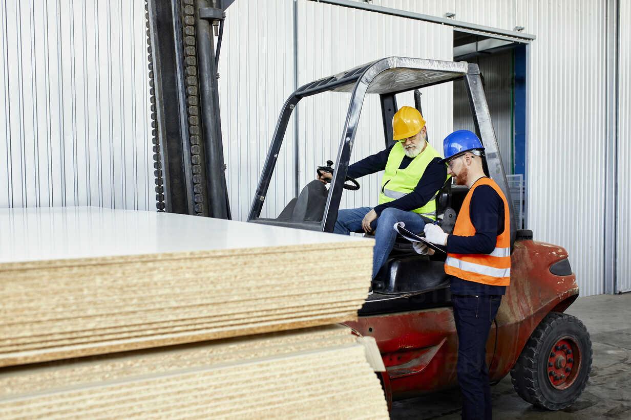 Man talking to worker on forklift in factory - ZEDF02159 - Zeljko Dangubic/Westend61