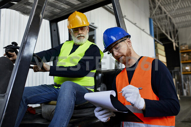 Man talking to worker on forklift in factory - ZEDF02162 - Zeljko Dangubic/Westend61