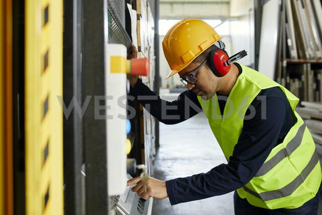 Man operating machine in industrial factory - ZEDF02174