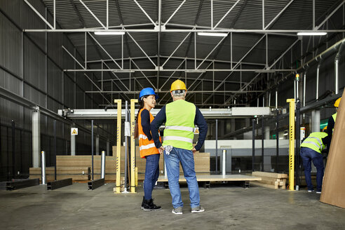 Rear view of male and female worker standing in factory workshop - ZEDF02180