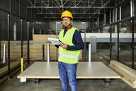 Portrait of worker with clipboard in factory warehouse - ZEDF02195