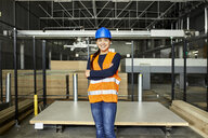 Portrait of smiling female worker in factory warehouse - ZEDF02198