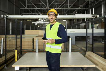 Portrait of smiling worker with tablet in factory warehouse - ZEDF02201