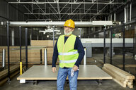 Portrait of smiling mature worker in factory warehouse - ZEDF02204