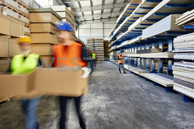 Workers moving and carrying boxes in factory warehouse - ZEDF02222 - Zeljko Dangubic/Westend61