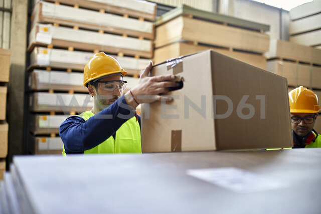Worker carrying box in factory warehouse - ZEDF02225