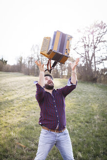 Bearded man throwing accordion in the air on a meadow - HMEF00344
