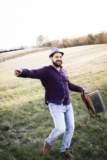 Portrait of bearded man with accordion dancing on a meadow - HMEF00347