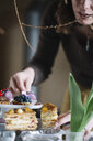 Woman arranging pastry on cake stand - ALBF00854