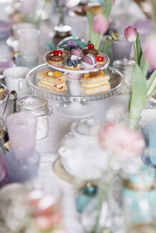 Laid table with pastries on cake stand and floral decoration at springtime - ALBF00863