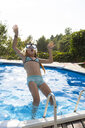 Girl jumping into swimming pool - HSIF00536