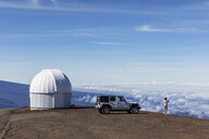 USA, Hawaii, Mauna Kea volcano, woman in front of off road vehicle at observatory - FOF10664