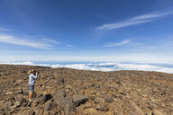 USA, Hawaii, Mauna Kea volcano, female tourist taking a photo of volcanic landscape - FOF10682