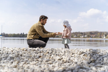 Germany, Bavaria, Herrsching, father and daughter on pebble beach at lakeshore - DIGF06741