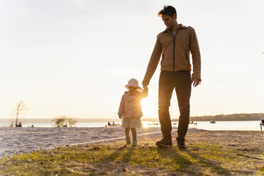 Germany, Bavaria, Herrsching, father and daughter walking at the lakeshore at sunset - DIGF06744