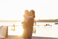 Germany, Bavaria, Herrsching, mother carrying daughter at the lakeshore at sunset - DIGF06747
