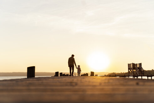 Germany, Bavaria, Herrsching, father and daughter walking on jetty at sunset - DIGF06750
