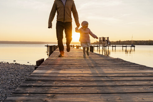 Germany, Bavaria, Herrsching, father and daughter walking on jetty at sunset - DIGF06753
