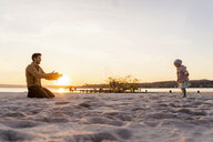 Germany, Bavaria, Herrsching, father and daughter playing on the beach at sunset - DIGF06756