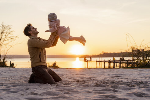 Germany, Bavaria, Herrsching, father and daughter playing on the beach at sunset - DIGF06759