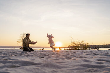 Germany, Bavaria, Herrsching, father and daughter playing on the beach at sunset - DIGF06762