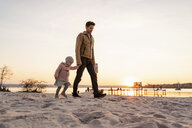 Germany, Bavaria, Herrsching, father and daughter walking on the beach at sunset - DIGF06765