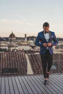 Italy, Florence, stylish man on roof terrace at sunset - FBAF00374