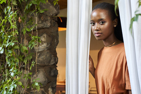 Woman looking through the window curtains. Botanica, Moçambique, Maputo. - VEGF00027
