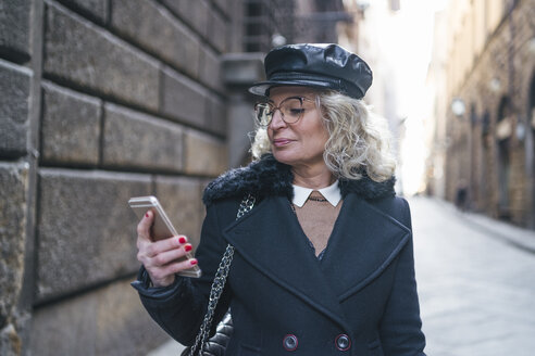 Mature woman wearing black coat and leather cap looking at cell phone - FBAF00380