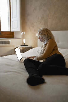 Mature businesswoman lying on bed working on laptop - FBAF00395