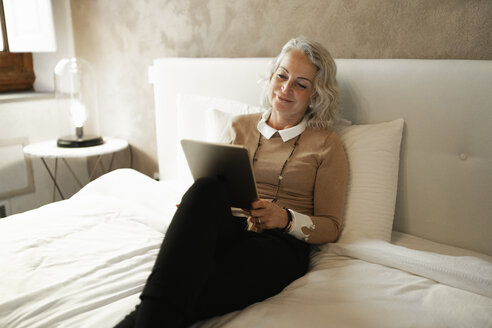 Portrait of content mature businesswoman sitting on bed looking at digital tablet - FBAF00407