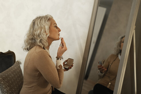 Profile of mature businesswoman applying makeup - FBAF00413